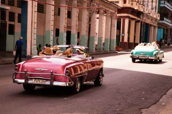 girls riding on red convertible coupe